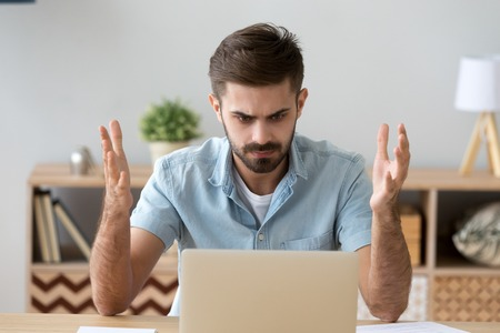 L'uomo frustrato e fastidioso seduto alla scrivania in ufficio usando il computer, guardando il laptop rotto rotto, prova rabbia e indignazione. Il maschio preoccupato ha problemi con la password di verifica o il concetto di perdita di dati Archivio Fotografico