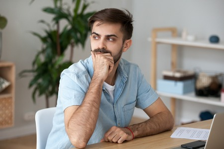 Thoughtful young millennial man sitting at the desk in office or home looking away contemplating. Handsome serious male student thinking about new idea or project analysing making decision concept Stock Photo