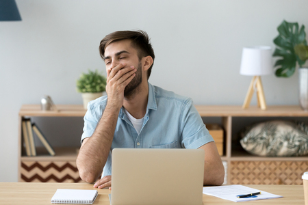 Exhausted or bored male sitting at the desk in office room. Worker or student man yawning covering mouth with hand, feels tired after hard working day. Fatigue lack of energy and overworking concept