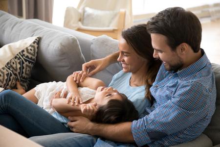 Famille heureuse multiethnique assise sur un canapé dans le salon. Des parents aimants qui passent du temps libre dans une nouvelle maison avec une adorable petite fille d'âge préscolaire. Déménagement déménagement ou concept de prêt hypothécaire