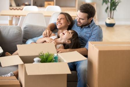 La famiglia multietnica trascorre del tempo insieme seduta sul divano in soggiorno e si diverte a giocare con la piccola figlia in età prescolare circondata da scatole di cartone a casa. Acquisto di un nuovo concetto di mutuo per trasloco di casa house