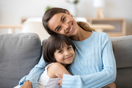 Head shot portrait smiling mulatto mother embrace little daughter sitting together on sofa posing looking at camera at home happy motherhood love and tenderness warm relationships between kid and mom.