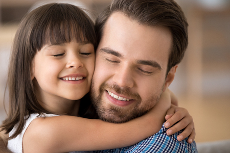 Close up portrait pretty mulatto daughter embracing Caucasian father sitting on couch at home. Multi-ethnic people with closed eyes enjoy spend time together. Happy diverse multiracial family concept