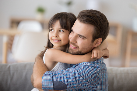 Head shot diverse mulatto preschool daughter sitting on sofa together with caucasian young father and hugging. Support protection and warm relations between dad and kid, daddy is best friend concept 免版税图像