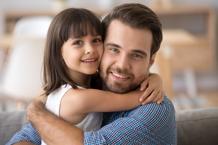 Close up portrait multiracial diverse family little adorable preschool daughter embrace loving handsome dad. Daddy hugging kid expressing support love devotion and protection. Happy father day concept Stock Photo