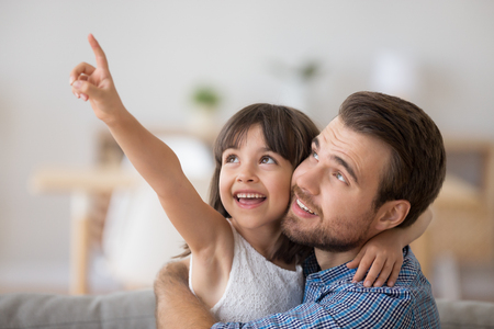 Multi-ethnic diverse happy family child and daddy sitting on couch together in living room at home. Preschool adorable positive daughter embracing with young father pointing with her hand upper left
