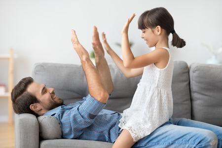 Joyeuse famille diversifiée positive à la maison, jeune père souriant allongé sur un canapé s'amusant avec sa fille jouant au jeu de pat-a-cake en frappant des mains en donnant cinq coups. Concept d'activités de loisirs de week-end en famille