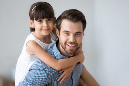 Head shot laughing diverse attractive family have fun play at home together. Portrait of happy little adorable sweet daughter piggyback her young handsome father man carrying loving child on his back