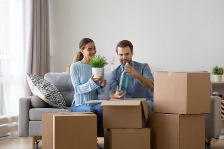 Married diverse couple sitting together on sofa in living room at new modern home unpack belongings from cardboard boxes wife hold flower pot, husband hold decorative glass bottle. Moving day concept Banque d'images
