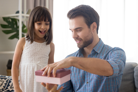 Little adorable preschool daughter prepares for daddy gift at fathers day. Dad receive from child unexpected surprise open pink gift box feels happy and glad sitting on couch in living room at home