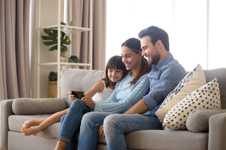 Married diverse couple spend free time on weekend with small daughter sitting on sofa in living room at home. Positive mom daddy little kid use smartphone watching cartoons videos online having fun