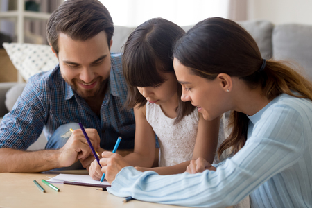 Happy multi-ethnic family have fun spend time together at home. Mulatto daughter mother and Caucasian father drawing on paper sitting at table with coloured pencils closeup. Leisure activities concept 版權商用圖片