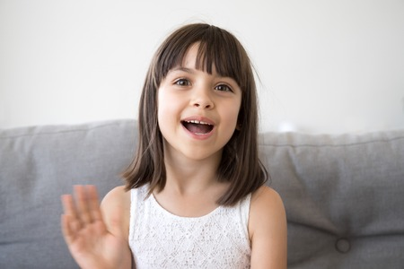 Small girl sitting on couch alone at home. Head shot portrait little adorable daughter waving hand looking at camera smile saying hello or goodbye. First acquaintance and online communication concept Stock fotó