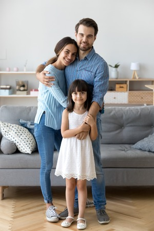 Full length diverse multi-ethnic family married couple wife husband little daughter embracing standing together in living room smiling looking at camera at new modern home feels happy and satisfied.