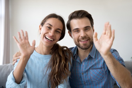 Head shot married couple sitting on sofa at home. Portrait wife and husband waving hands looking at camera smiling saying hello greeting or goodbye. First acquaintance or online communication concept Imagens