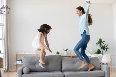 Full length positive mother and little daughter having fun jumping together on sofa in living room at home. Adorable girl playing enjoying active weekends with elder sister nanny or loving mom indoors Imagens