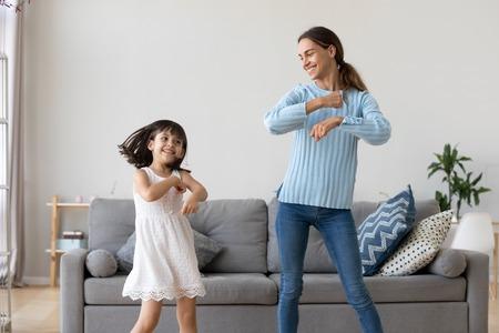 Madre allegra piccola figlia in piedi nel soggiorno di casa che si muove ballando insieme alla canzone preferita. Il bambino si diverte con la tata della sorella maggiore o con la madre amorevole concetto di tempo libero e stile di vita attivo Archivio Fotografico
