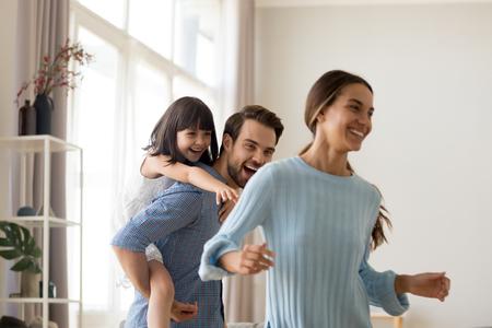 Junger glücklicher Vater, der lacht, die kleine Tochter huckepack tragend, die Mutter fängt, die mit der unterschiedlichen Familie spielt, die zusammen Spaß hat. Kind, das aktives Spiel mit Eltern im Wohnzimmer zu Hause genießt