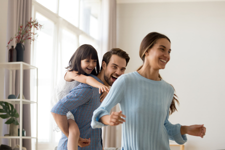 Young happy father laughing carrying on back piggybacking little daughter catching mum playing with diverse family having fun together. Kid enjoying active game with parents in living room at home