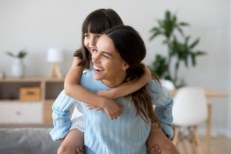 Cheerful diverse active family have fun play in living room at home. Happy little adorable sweet daughter piggybacks her young attractive mother. Mom carrying loving kid on her back laughing together