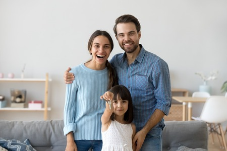 Diverse family at new home. Little preschool daughter holds in hand keys standing with young parents mother and father in living room smiling looking at camera. Moving relocate at new house concept