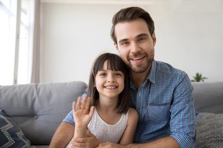 Kopfschussporträt eines fröhlichen, vielfältigen jungen Mannes, der zu Hause mit seiner Tochter auf dem Sofa sitzt, hat einen Videoanruf mit dem Computer, winkt mit den Händen oder verabschiedet sich von einem Freund und lächelt in die Kamera