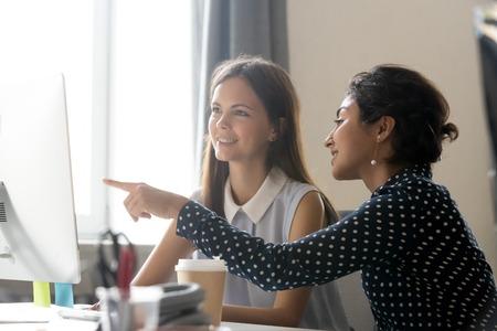 Sorridenti colleghi millenari diversi che discutono di lavoro online insieme, felice stagista caucasica che ascolta il mentore indiano che spiega l'impiegato di formazione delle attività del computer, concetto di mentoring dell'ufficio
