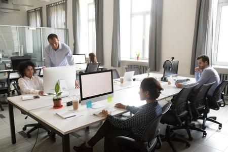 Diversos trabajadores multiétnicos trabajan juntos en un espacio de oficina moderno compartido, personas del equipo de proyectos creativos multirraciales que colaboran hablando usando computadoras en coworking, concepto de trabajo en equipo corporativo del personal Foto de archivo