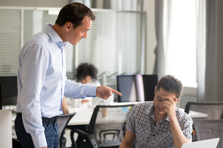 Angry boss ceo scolding rebuking incompetent office worker intern, dissatisfied team leader shouting pointing finger at lazy employee for bad work failure, reprimand or discrimination at work concept
