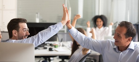 Excited euphoric male colleagues giving high five celebrating breakthrough, corporate success concept, happy motivated business men coworkers sharing victory, goal achievement, win or good result