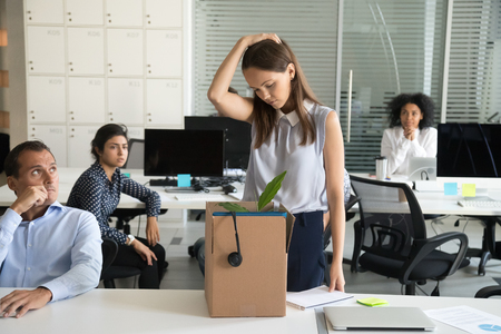 Upset female employee packing belongings in box, frustrated stressed girl getting fired from job ready to leave on last day at work, sad office worker desperate about unfair dismissal losing job Foto de archivo