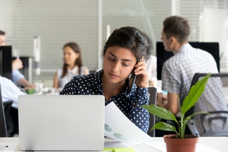 Serious millennial indian woman employee talking on the phone making call at work, young hindu female manager discussing business document by mobile sitting at shared office desk with laptop Stock Photo
