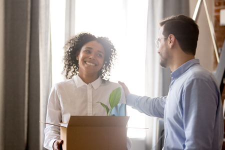 Smiling hired african female employee holding box with belongings excited about friendly welcoming of male boss expressing support respect to new worker on first working day in multi-ethnic office. Stock Photo - 111160757