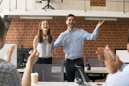 Aufgeregter Firmenchef oder Teamleiter stellt Kollegen im Büro einen neuen Mitarbeiter vor Standard-Bild