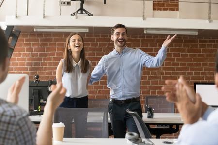 Opgewonden bedrijfsbaas of teamleider die nieuwe werknemer voorstelt aan collega's op kantoor die ingehuurd nieuwkomerslid verwelkomen, feliciteren met promotie, applaudisseren voor het vieren van beloning, ondersteunende collega Stockfoto