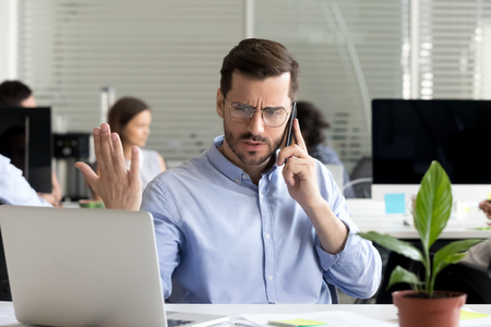 Angry business man talking on phone disputing looking at laptop, stressed frustrated office worker arguing by mobile solving online computer problem with technical support complaining on bad service Stock Photo