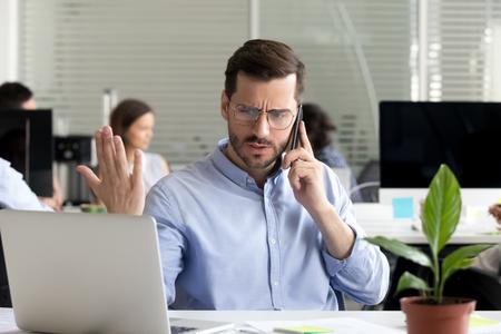Zły człowiek biznesu rozmawia przez telefon, kłócąc się, patrząc na laptopa, zestresowany sfrustrowany pracownik biurowy kłócący się przez telefon komórkowy rozwiązujący problem z komputerem online z pomocą techniczną, skarżący się na złą obsługę