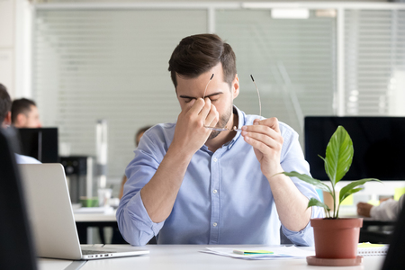 Tired businessman taking off glasses lost productivity after office work laptop use to relieve dry irritated eyes feeling fatigue tension or strain, chronic computer syndrome, bad weak vision problem Stockfoto