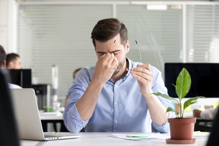 Un homme d'affaires fatigué enlevant des lunettes a perdu sa productivité après l'utilisation d'un ordinateur portable pour soulager les yeux secs et irrités, sensation de fatigue, de tension ou de fatigue, syndrome informatique chronique, mauvais problème de vision faible