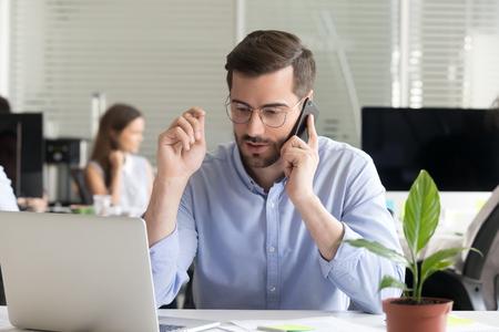 Marketing verkoopmanager consulting klant die aanbieding doet verkopen praten over de telefoon in de buurt van laptop in kantoor, serieuze zakenman die belt onderhandelen sprekend door mobiel houden interview op mobiele telefoon Stockfoto