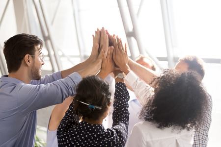 Diverse business team associates office workers group giving high five together as concept of coaching, teamwork involvement, engaging in teambuilding, motivated by unity, good corporate relations