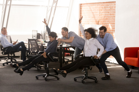 Carefree excited diverse workers having fun riding oh chairs celebrating friday together, happy employees enjoy funny competition laughing together feel great at work break, friendly office team game