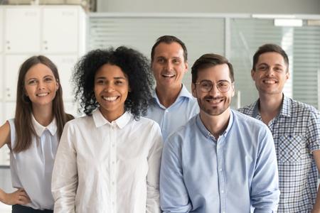 Groupe d'employés de bureau souriants et diversifiés, employés professionnels multiraciaux heureux regardant la caméra, hommes d'affaires motivés posant ensemble, portrait de l'équipe de vente de main-d'œuvre multiethnique