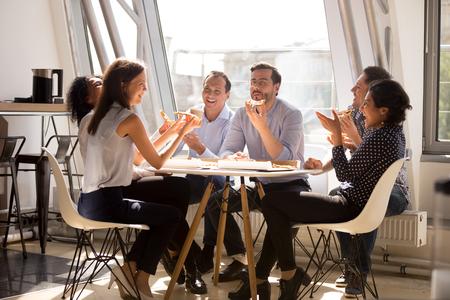 Vriendelijke gelukkige diverse teamwerkers praten lachend samen pizza eten op kantoor, vrolijke werknemers personeelsgroep chatten delen maaltijd genieten van plezier op het werk, goede relaties tijdens de lunchpauze Stockfoto