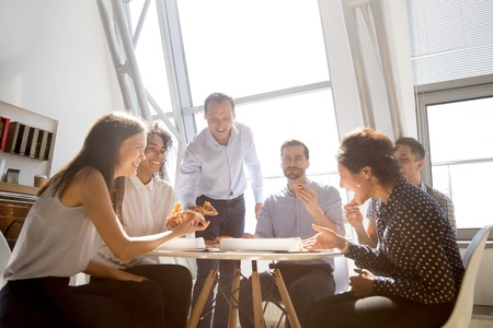 Cheerful diverse team people workers students laughing at funny joke while eating pizza together, friendly multi-ethnic colleagues group talking enjoying having fun and corporate lunch in office room Stockfoto