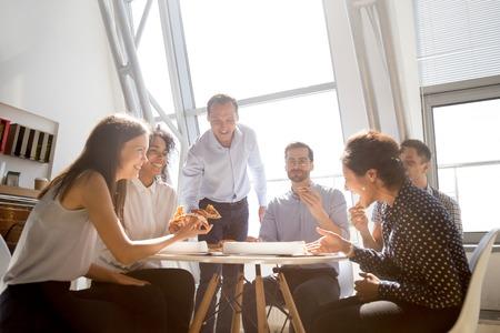 Fröhliche, vielfältige Teammitarbeiter, Studenten, die über lustigen Witz lachen, während sie zusammen Pizza essen, freundliche multiethnische Kollegen, die sich unterhalten, Spaß haben und im Büro zu Mittag essen