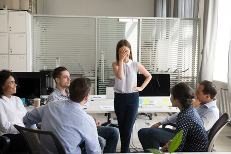 Shy nervous bashful female employee feels embarrassed blushing afraid of public speaking at corporate group team meeting, timid stressed woman hiding face during awkward moment reporting in office Foto de archivo - 111160854