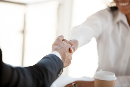 Close up of diverse happy workers shake hands greeting at business meeting in office, colleagues handshake getting acquainted at briefing, partners introduce making good first impression Stockfoto