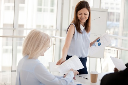 Smiling millennial female mentor or coach give handouts to employees at teambuilding or training in office, young woman share paperwork plan or report to colleagues at briefing or business meeting