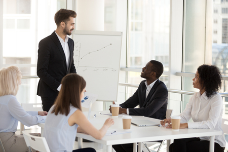 Smiling male employee give flipchart presentation at briefing with colleagues, positive mentor or coach present strategy or successful plan on whiteboard, interact with workers during office meeting
